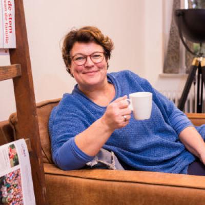 Vrouw met kopje koffie in stoel