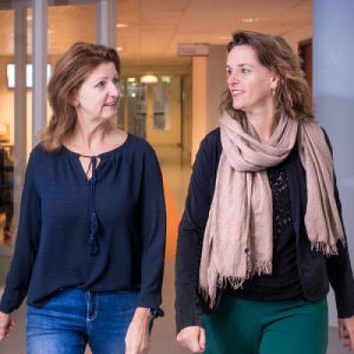 Twee vrouwen lopen door de hal